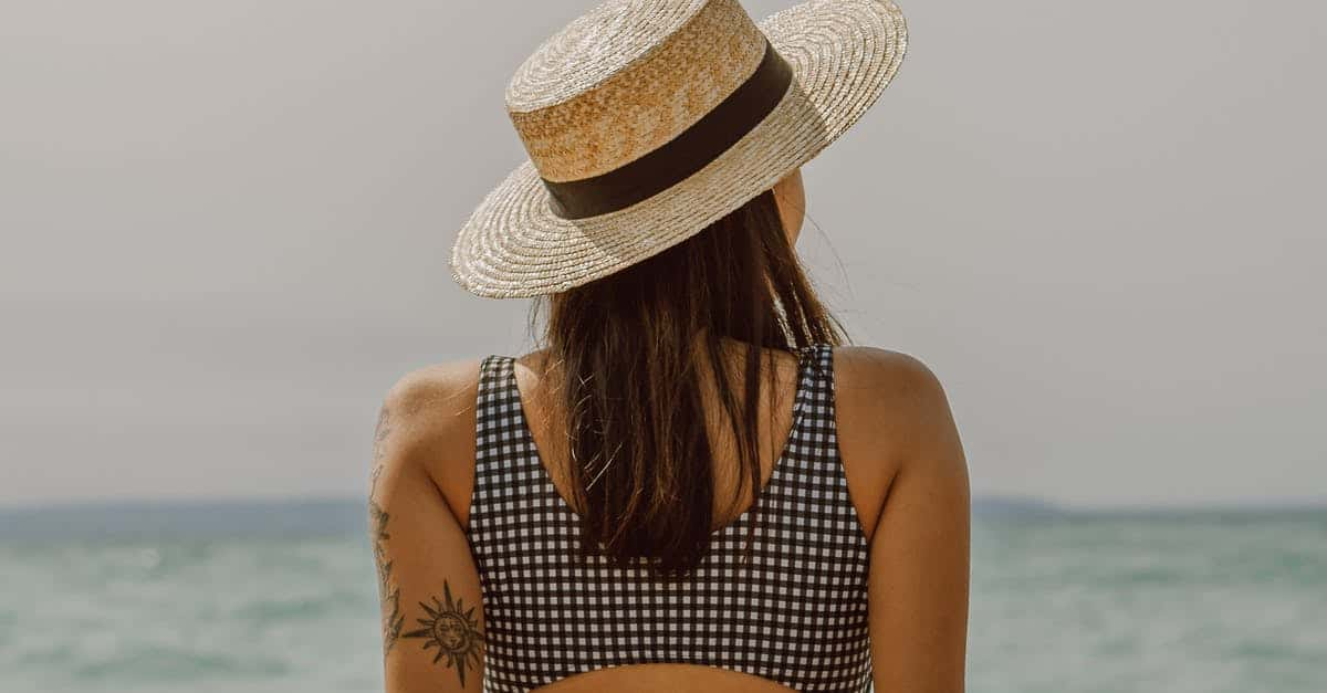 A woman wearing a hat and a body of water