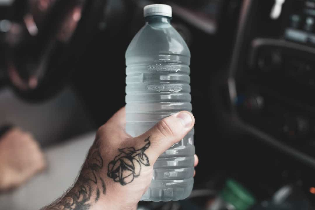 A hand holding a bottle