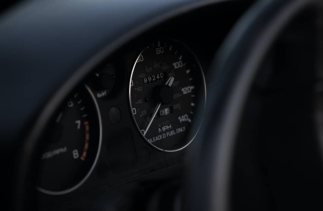 A clock hanging from the side of a car